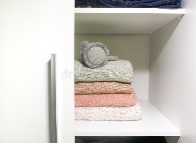 Άσπρο ράφι της εγχώριας ντουλάπας με τα ζωηρόχρωμα πουλόβερ, τους άλτες και τα θερμά ακουστικά Μικρή διαστημική οργάνωση στοκ φωτογραφία με δικαίωμα ελεύθερης χρήσης