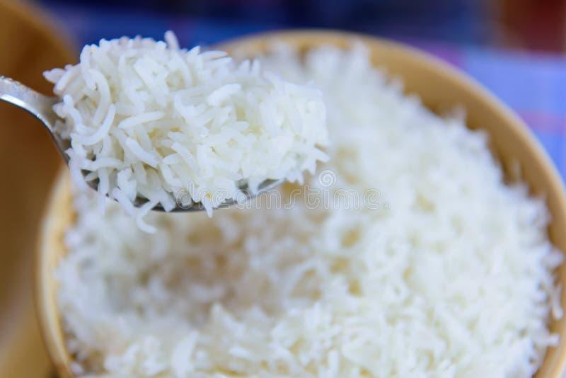 Άσπρο ρύζι ατμού σε μια μακρο λεπτομέρεια και ένα υπόβαθρο κουταλιών στοκ εικόνες με δικαίωμα ελεύθερης χρήσης