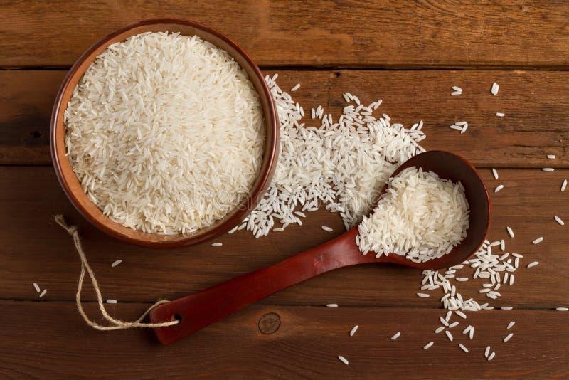 Άσπρο ρύζι σε ένα κεραμικό κύπελλο και κουτάλι σε έναν ξύλινο πίνακα στοκ φωτογραφία