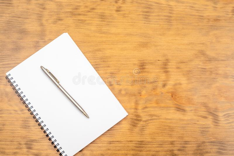 Άσπρο σημειωματάριο με τη μάνδρα χάλυβα σε έναν ξύλινο πίνακα r στοκ εικόνες