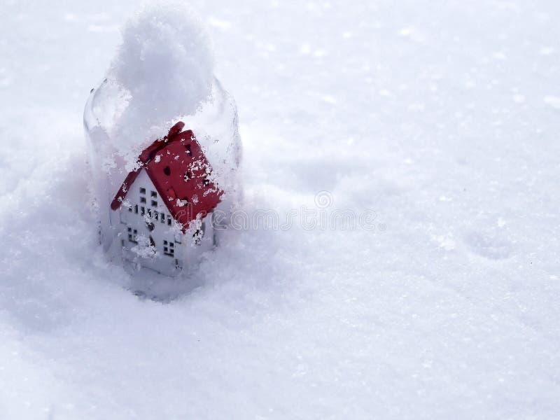 Άσπρο σπίτι παιχνιδιών με μια κόκκινη στέγη στο χιόνι ενάντια στο σκηνικό του χειμερινού τοπίου, η έννοια των συγχαρητηρίων στο S στοκ εικόνα