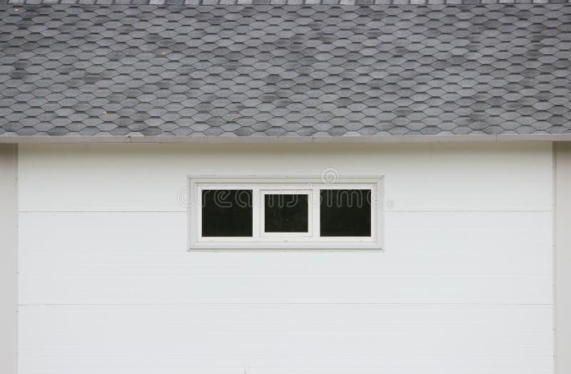 Άσπρο σπίτι σύστασης τοίχων, σκοτεινά παράθυρα, εύκαμπτο γκρίζο υπόβαθρο κεραμιδιών ελεύθερη απεικόνιση δικαιώματος