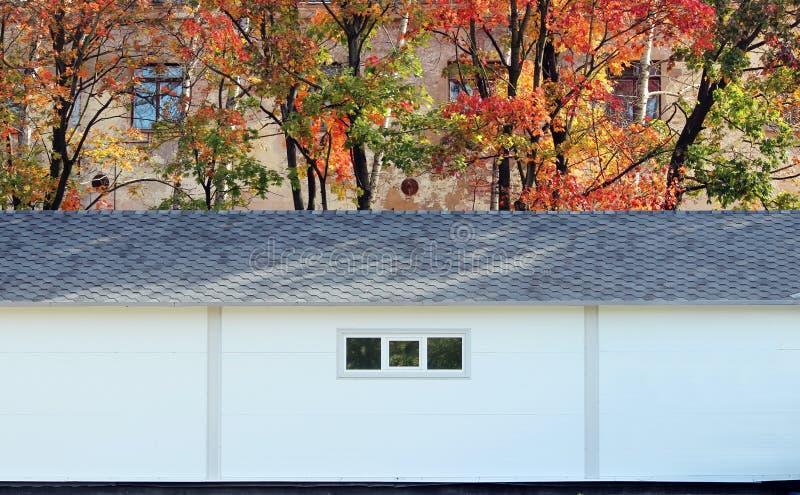 Άσπρο σπίτι σύστασης τοίχων, σκοτεινό κιβώτιο, εύκαμπτα καφετιά κεραμίδια στο υπόβαθρο του πολύχρωμου δάσους φθινοπώρου φύλλων ελεύθερη απεικόνιση δικαιώματος