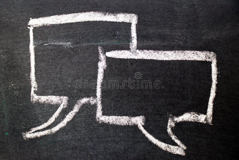 Άσπρο σχέδιο κιμωλίας ως ομιλία φυσαλίδων στο μαύρο υπόβαθρο πινάκων στοκ εικόνα