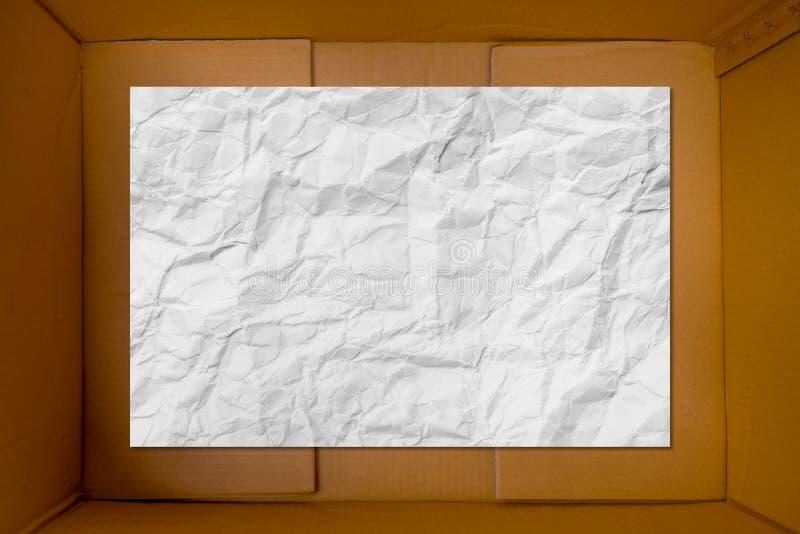 Άσπρο τσαλακωμένο έγγραφο στο χαρτοκιβώτιο χαρτονιού ως υπόβαθρο στοκ φωτογραφίες με δικαίωμα ελεύθερης χρήσης