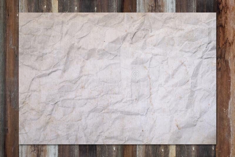 Άσπρο τσαλακωμένο κενό έγγραφο για τον ξύλινο πίνακα grunge στοκ εικόνα