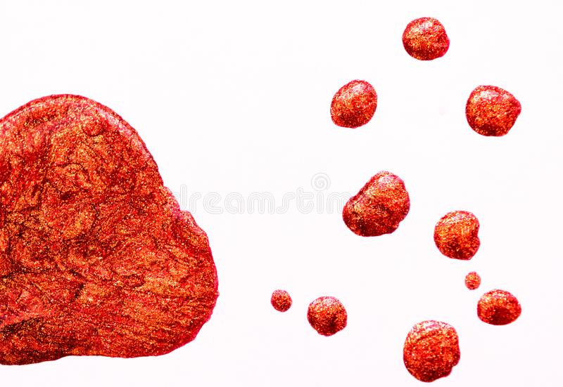 Άσπρο υπόβαθρο με τις πτώσεις της κόκκινος-πορτοκαλιάς ιριδίζουσας στιλβωτικής ουσίας καρφιών στοκ εικόνα με δικαίωμα ελεύθερης χρήσης
