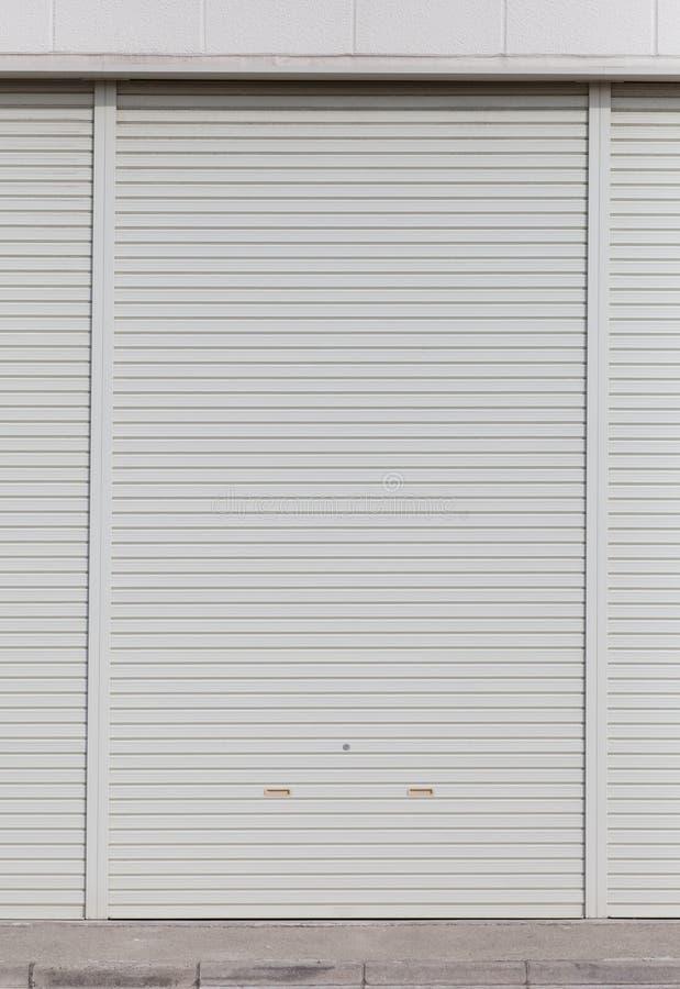 Άσπρο υπόβαθρο παραθυρόφυλλων πορτών κυλίνδρων μετάλλων στοκ φωτογραφίες