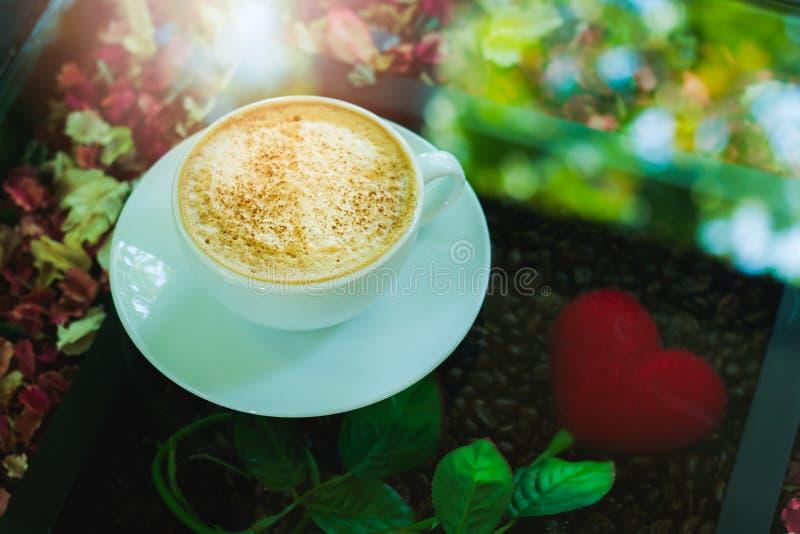 Άσπρο φλυτζάνι καφέ με τον αφρό γάλακτος που τοποθετείται στον πίνακα γυαλιού με την κόκκινη καρδιά στοκ εικόνα με δικαίωμα ελεύθερης χρήσης