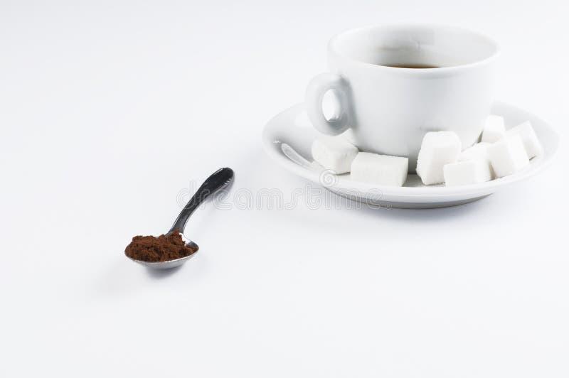 Άσπρο φλυτζάνι καφέ με τους κύβους ζάχαρης και κουτάλι μετάλλων που απομονώνεται στο άσπρο υπόβαθρο r στοκ εικόνες με δικαίωμα ελεύθερης χρήσης