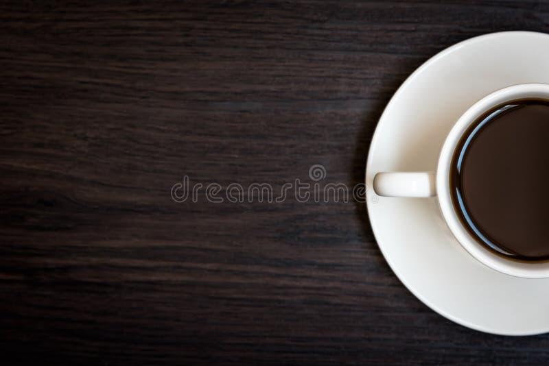 Άσπρο φλυτζάνι καφέ στο ξύλινο επιτραπέζιο υπόβαθρο με το διαστημικό, μισό φλυτζάνι αντιγράφων με το σύνολο του καφέ, τη σκοτεινή στοκ εικόνα με δικαίωμα ελεύθερης χρήσης