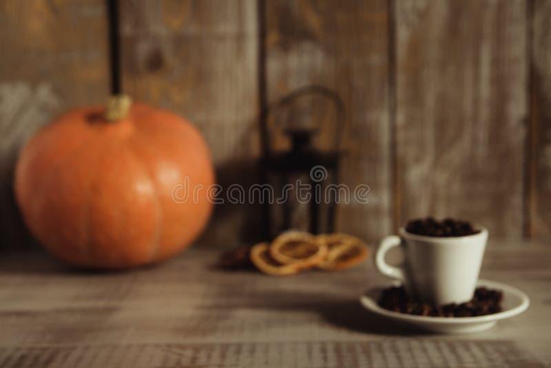 Άσπρο φλυτζάνι που γεμίζουν με τα φασόλια καφέ σε έναν ξύλινο πίνακα στοκ εικόνες
