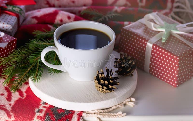 Άσπρο φλυτζάνι του καυτού καφέ στο άσπρο υποβάθρου κόκκινο δώρο προγευμάτων πρωινού Χριστουγέννων κώνων Χριστουγέννων μάλλινο άσπ στοκ εικόνα με δικαίωμα ελεύθερης χρήσης