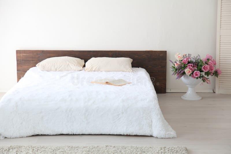 Άσπρο φωτεινό εσωτερικό κρεβατοκάμαρων με το κρεβάτι στοκ φωτογραφία με δικαίωμα ελεύθερης χρήσης