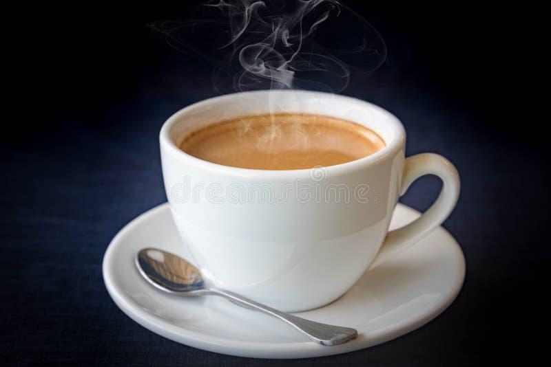 Άσπρο φλιτζάνι του καφέ στο σκούρο μπλε υπόβαθρο στοκ εικόνες
