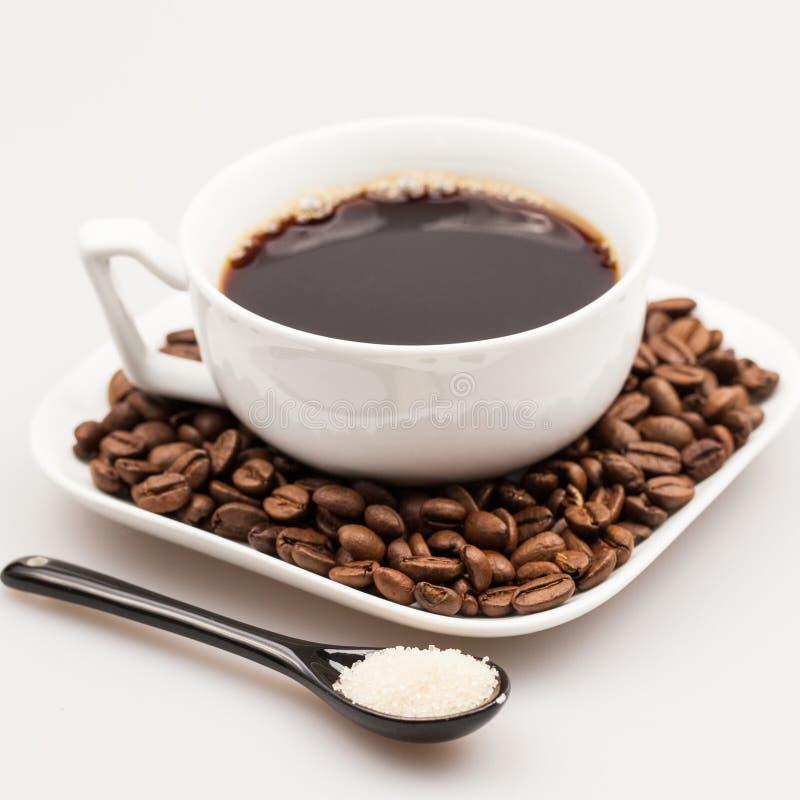 Άσπρο φλυτζάνι καφέ με τον καφέ, πιάτο με τα φασόλια καφέ και μαύρο κουταλάκι του γλυκού με τη ζάχαρη στοκ φωτογραφία με δικαίωμα ελεύθερης χρήσης