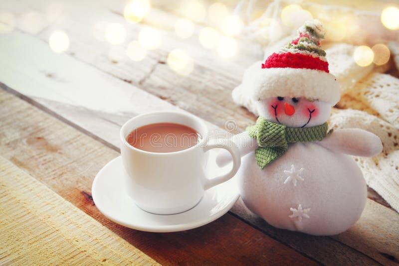 Άσπρο φλυτζάνι με τα καυτά φω'τα σοκολάτας, χιονανθρώπων και Χριστουγέννων στοκ φωτογραφία με δικαίωμα ελεύθερης χρήσης