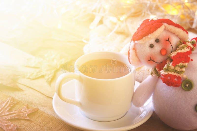 Άσπρο φλυτζάνι με τα καυτά φω'τα σοκολάτας, χιονανθρώπων και Χριστουγέννων στοκ φωτογραφίες
