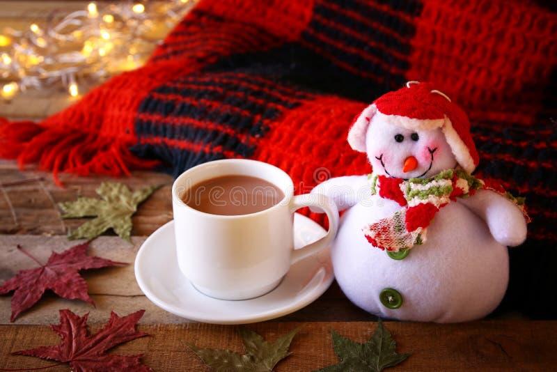 Άσπρο φλυτζάνι με τα φω'τα σοκολάτας, χιονανθρώπων και Χριστουγέννων στοκ εικόνες