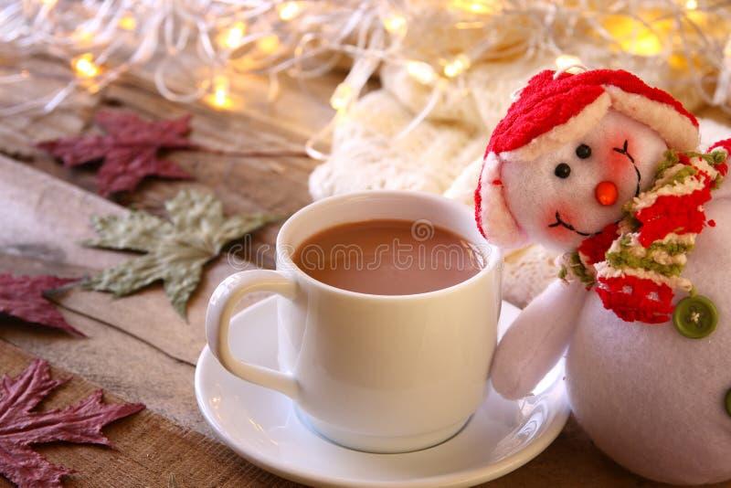Άσπρο φλυτζάνι με τα φω'τα σοκολάτας, χιονανθρώπων και Χριστουγέννων στοκ φωτογραφία