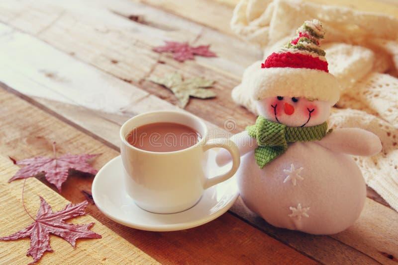 Άσπρο φλυτζάνι με την καυτούς σοκολάτα και το χιονάνθρωπο στοκ φωτογραφία