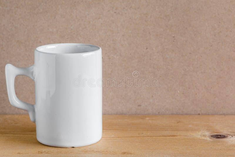 Άσπρο φλυτζάνι στον πίνακα στοκ εικόνες