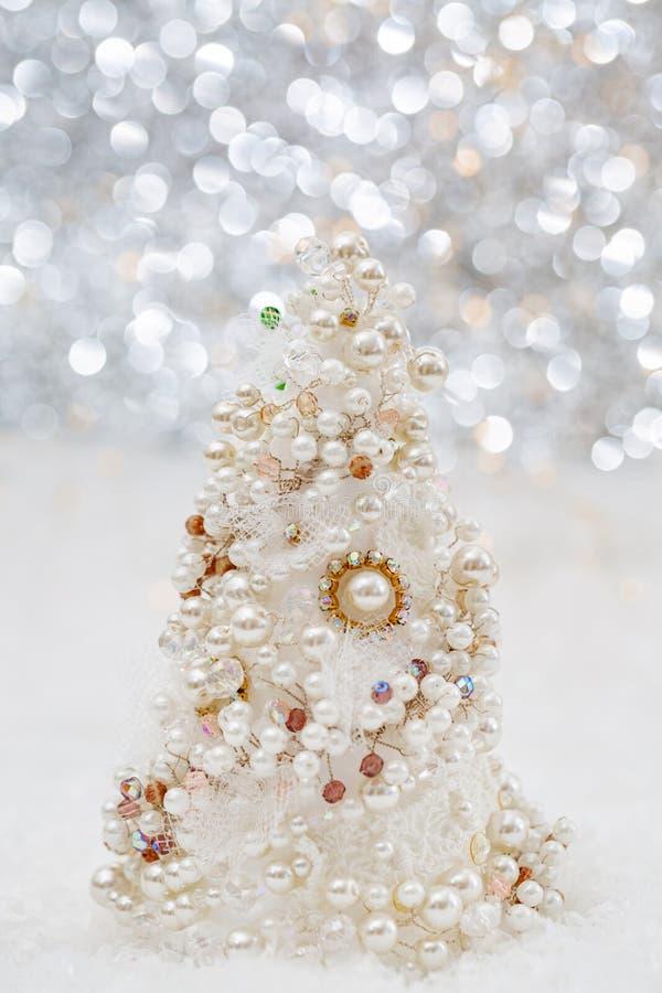 Άσπρο χριστουγεννιάτικο δέντρο με τα μαργαριτάρια και τις χάντρες στο χιόνι δίπλα στο όμορφο θολωμένο bokeh υπόβαθρο και την καμμ στοκ εικόνες
