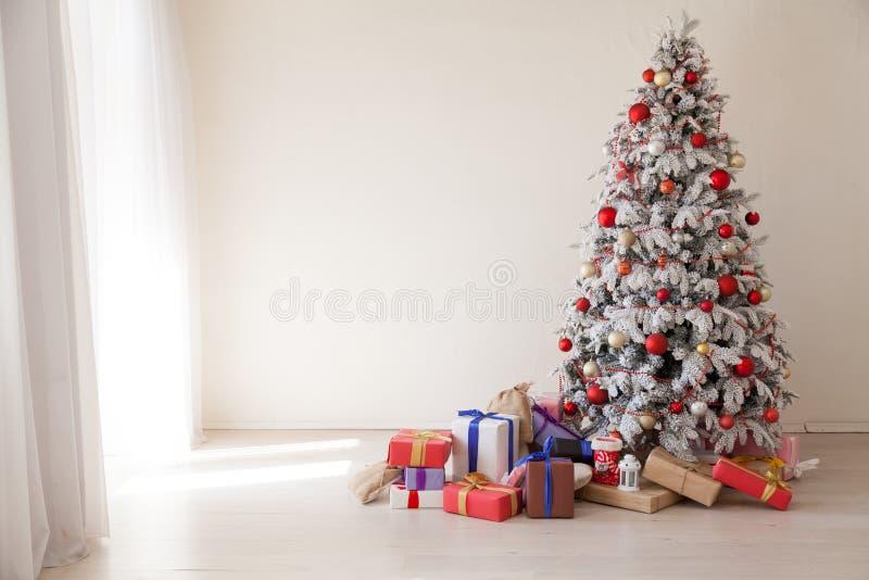 Άσπρο χριστουγεννιάτικο δέντρο με το κόκκινο ντεκόρ χειμερινών δώρων έτους παιχνιδιών νέο στοκ φωτογραφία με δικαίωμα ελεύθερης χρήσης