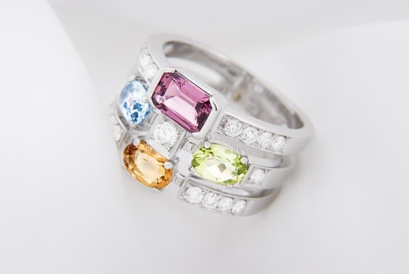 Άσπρο χρυσό δαχτυλίδι με το ψευδοτοπαζιακό peridot, το μπλε topaz, το ρόδινα tourmaline και τα διαμάντια στο μαλακό λευκό στοκ εικόνες