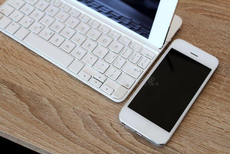 Άσπρο smartphone και άσπρη ταμπλέτα με το πληκτρολόγιο στοκ φωτογραφία
