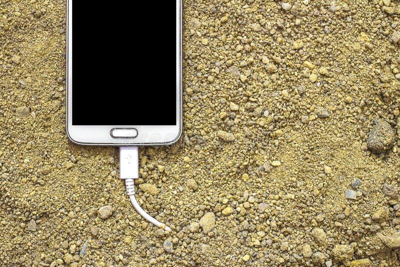 Άσπρο smartphone με έναν φορτιστή που συνδέεται με την άμμο μπροστινό και πίσω υπόβαθρο που θολώνεται στοκ φωτογραφίες