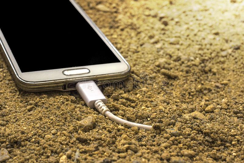 Άσπρο smartphone με έναν φορτιστή που συνδέεται με την άμμο μπροστινό και πίσω υπόβαθρο που θολώνεται στοκ φωτογραφία