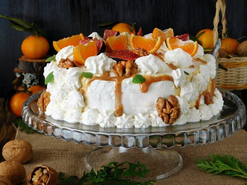Άσπρο torte που διακοσμείται με την κτυπημένες κρέμα, τα μανταρίνια, τα σύκα, το ξύλο καρυδιάς και την καραμέλα στοκ εικόνα με δικαίωμα ελεύθερης χρήσης