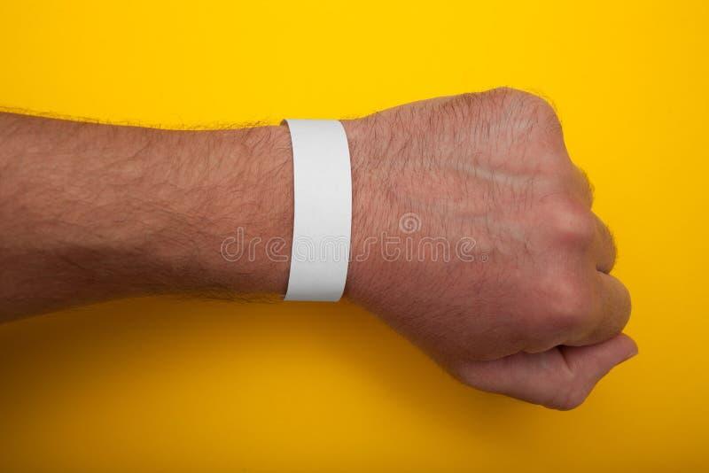 Άσπρο wristband, πρότυπο βραχιολιών για το γεγονός στο κίτρινο υπόβαθρο στοκ εικόνες