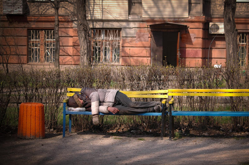 Άστεγοι ύπνοι ατόμων σε έναν πάγκο στοκ εικόνες με δικαίωμα ελεύθερης χρήσης