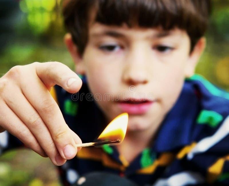 Άτακτο παιχνίδι αγοριών με το σπίρτο λαβής πυρκαγιάς στοκ εικόνα με δικαίωμα ελεύθερης χρήσης