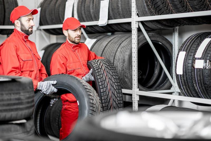 Άτομα που εργάζονται στην αποθήκη εμπορευμάτων με τις ρόδες στοκ φωτογραφία με δικαίωμα ελεύθερης χρήσης