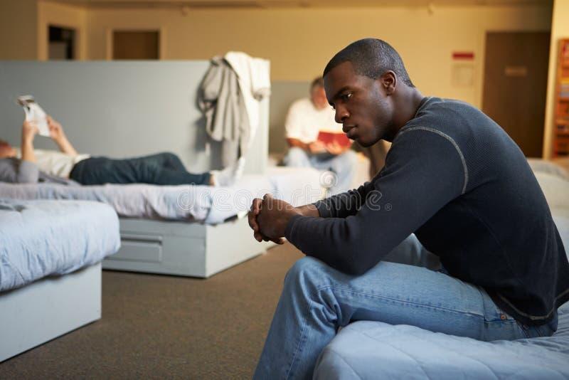 Άτομα που κάθονται στα κρεβάτια στο άστεγο καταφύγιο στοκ φωτογραφία με δικαίωμα ελεύθερης χρήσης