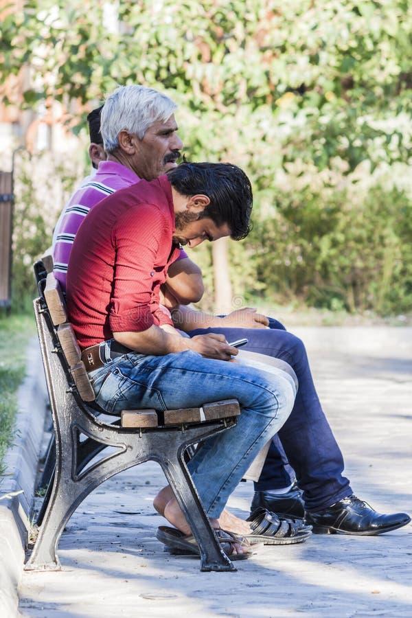 Άτομα που κάθονται στον πάγκο Το νεώτερο smartphone χρήσεων στοκ φωτογραφία