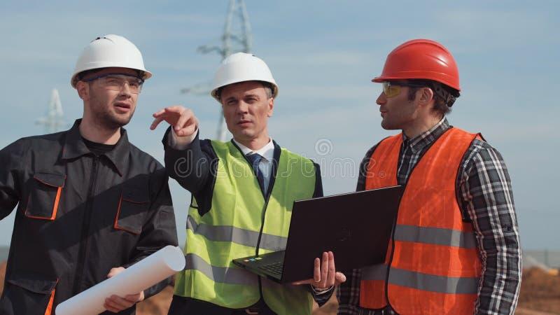 Άτομα στο εργοτάξιο που συζητούν το σχεδιάγραμμα στοκ εικόνα
