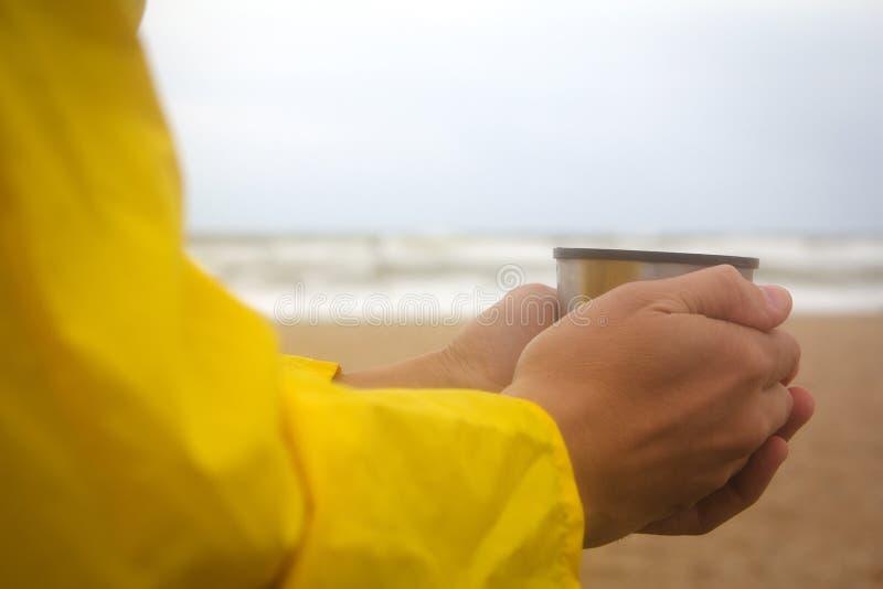 Άτομα στο κίτρινο αδιάβροχο στην παραλία πέρα από τη θυελλώδη θάλασσα που κρατά ένα φλυτζάνι του καυτού τσαγιού στοκ φωτογραφία με δικαίωμα ελεύθερης χρήσης