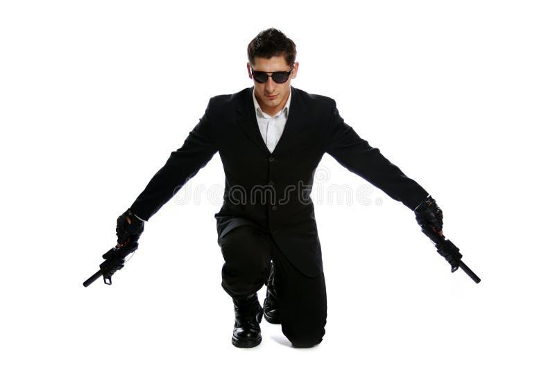 Άτομα στο μαύρο πυροβόλο όπλο εκμετάλλευσης κοστουμιών στοκ εικόνες