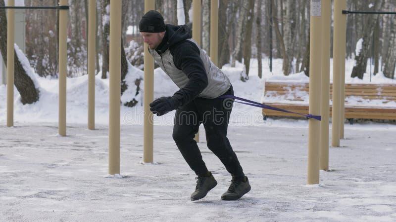 Άτομο αθλητών που κάνει crossfit την άσκηση με τον αποσυμπιεστή στην υπαίθρια χειμερινή κατάρτιση στοκ φωτογραφία