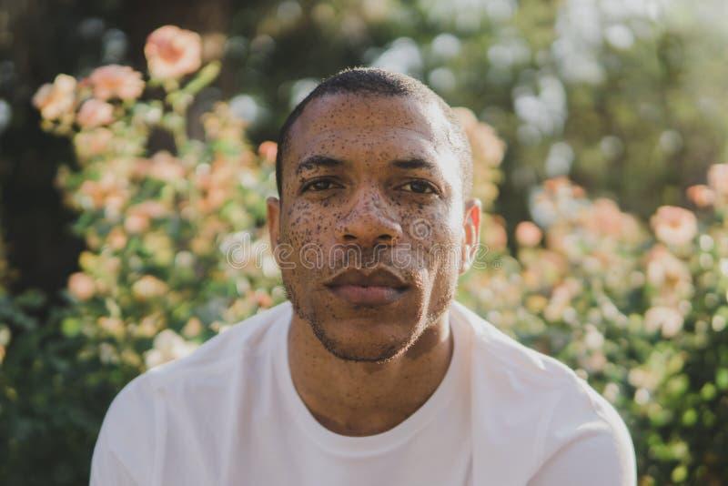 Άτομο αφροαμερικάνων με τις φακίδες που φαίνονται υπαίθρια σοβαρές στοκ φωτογραφίες