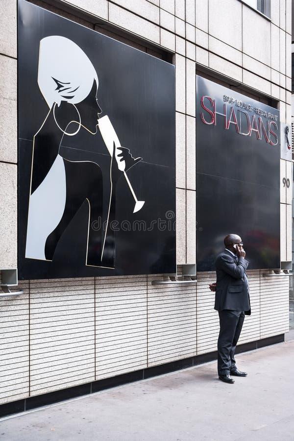 Άτομο αφροαμερικάνων που μιλά σε ένα κινητό τηλέφωνο στεμένος το β στοκ εικόνα