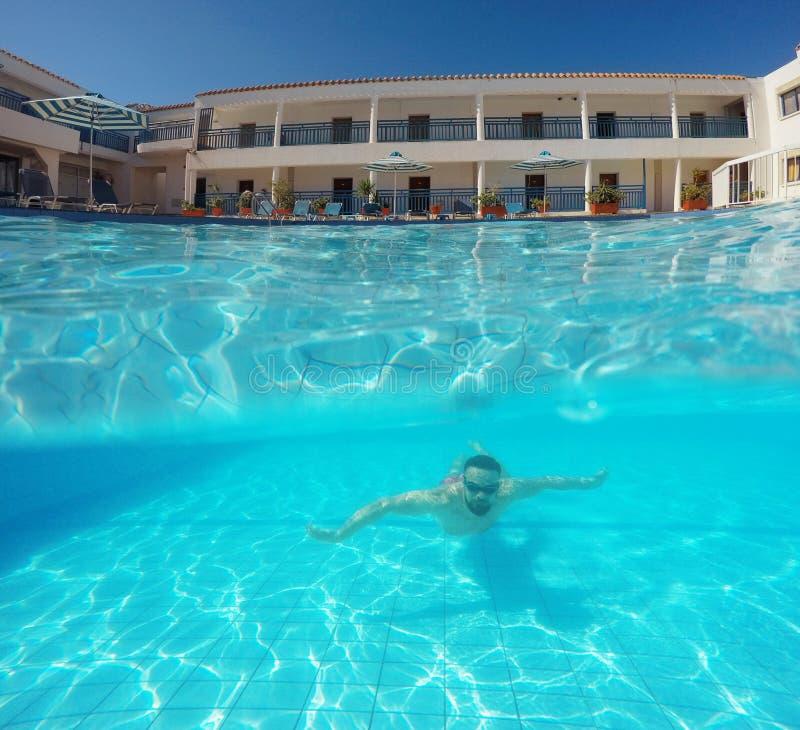 Άτομο γενειάδων με τα γυαλιά που κολυμπούν κάτω από το νερό στη λίμνη σε ένα tro στοκ φωτογραφία