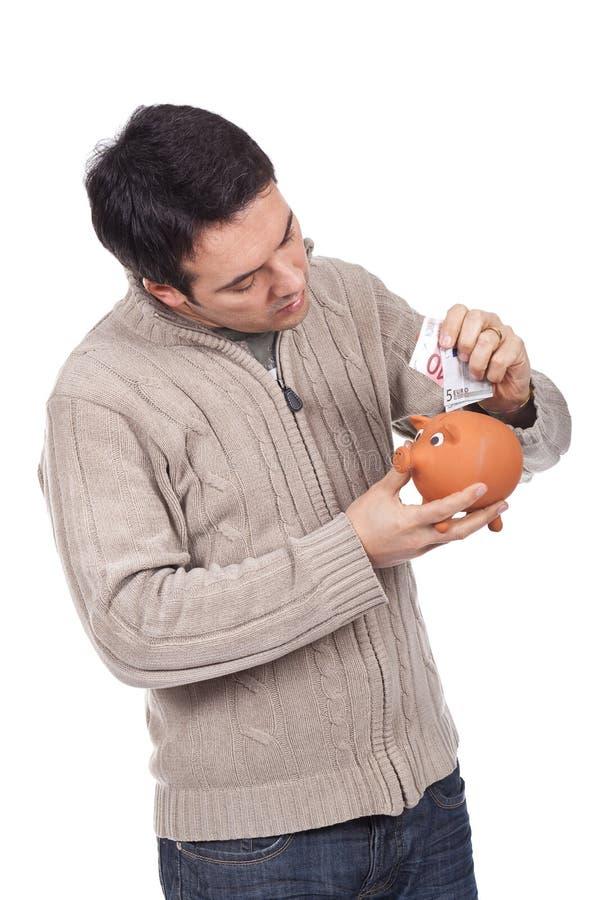 άτομο εκμετάλλευσης τραπεζών piggy στοκ εικόνα