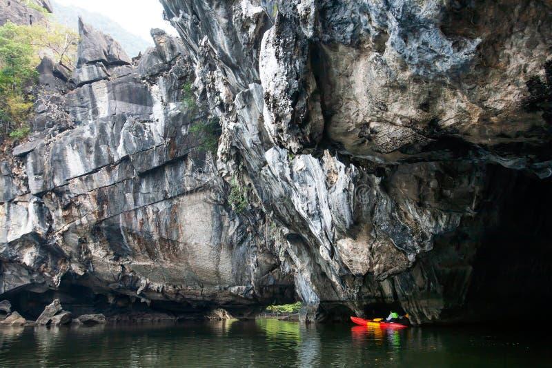 Άτομο εξερευνητών σακακιών ζωής μπροστά από τον απότομο απότομο βράχο ασβεστόλιθων στη θάλασσα στοκ φωτογραφίες