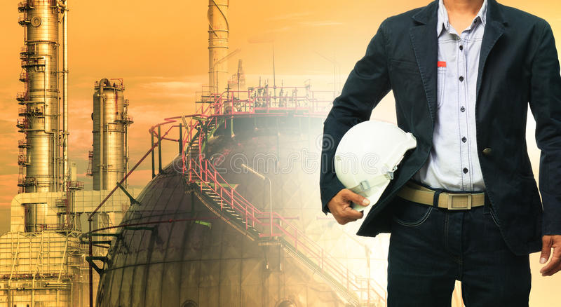 Άτομο εφαρμοσμένης μηχανικής και κράνος ασφάλειας που στέκεται ενάντια στο διυλιστήριο πετρελαίου στοκ φωτογραφία