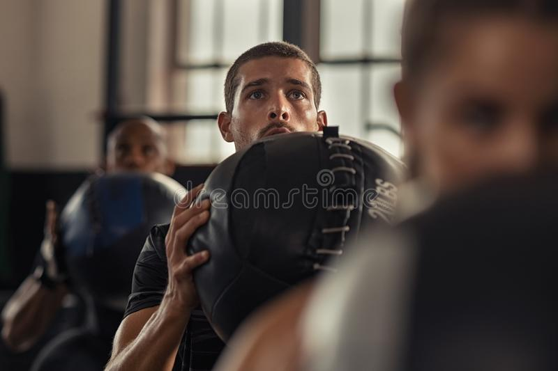Άτομο ικανότητας που κάνει τη στάση οκλαδόν με τη βαριά σφαίρα στοκ εικόνες